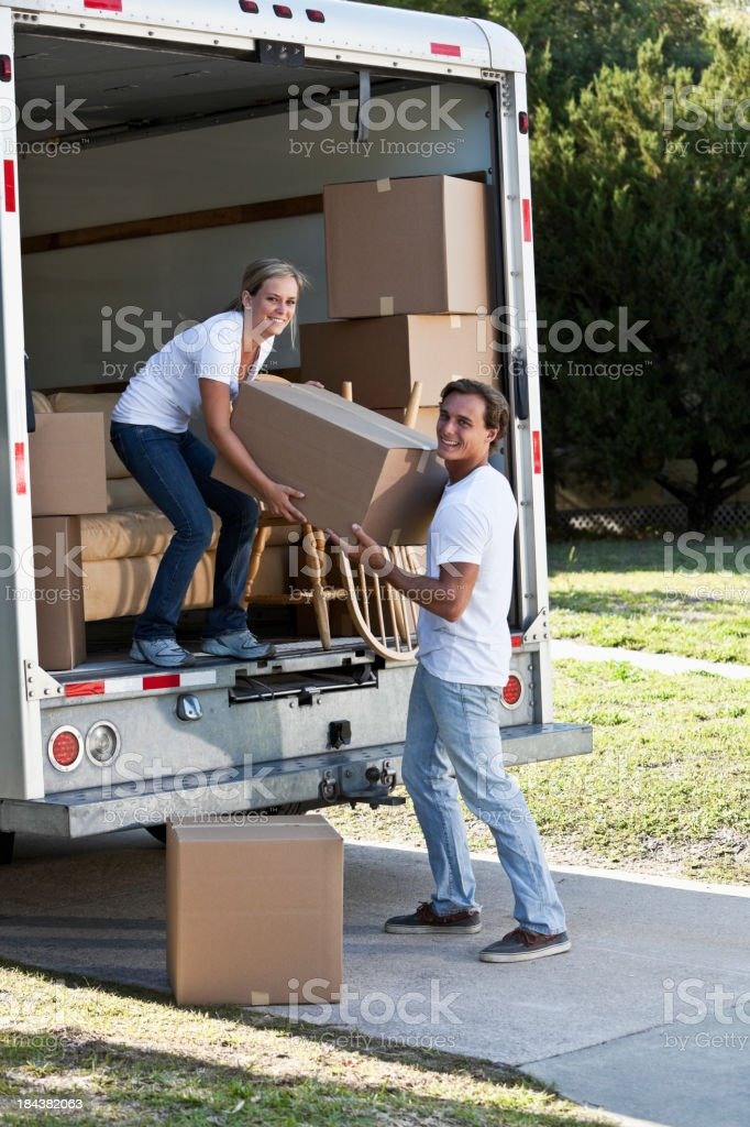 Young couple with moving van in driveway royalty-free stock photo