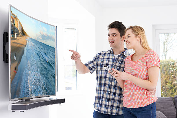 Young Couple With New Curved Screen Television At Home Young Couple With New Curved Screen Television At Home ultra high definition television stock pictures, royalty-free photos & images