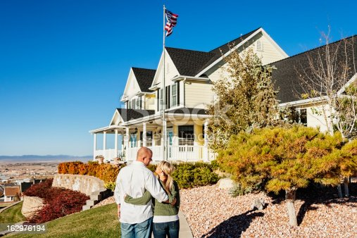 Photo of young couple standing on the walkway in front of their dream home, looking at one another optimistically.