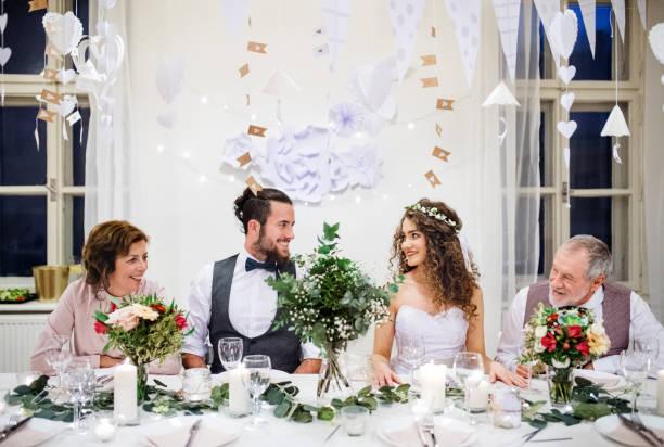 ein junges paar mit eltern auf eine hochzeit an einem tisch sitzen einander betrachtend. - bräutigam tisch stock-fotos und bilder