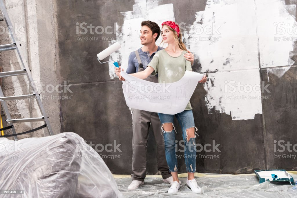 young couple with schemes and paint roller, renovation home concept royalty-free stock photo