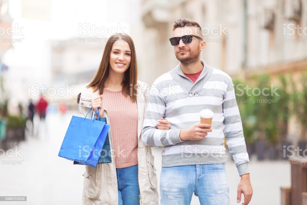 Young couple with shopping bag and coffee outdoors stock photo