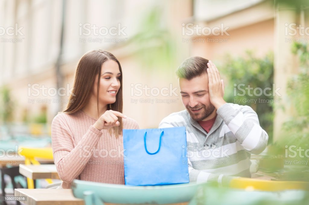 Young couple with shopping bag sitting outdoors stock photo