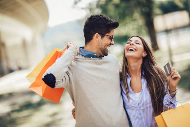 Young couple with shopping bags and credit card in the city Portrait of happy couple with shopping bags after shopping in city smiling and holding credit card credit card purchase stock pictures, royalty-free photos & images