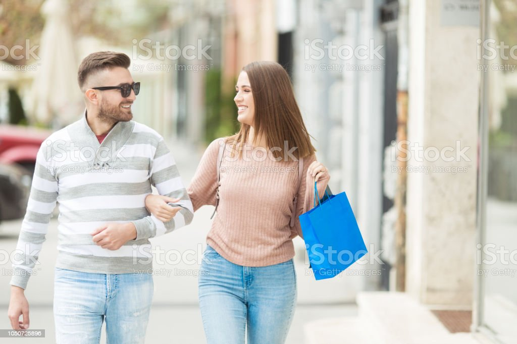 Young couple with shopping bags smiling and walking outdoors stock photo