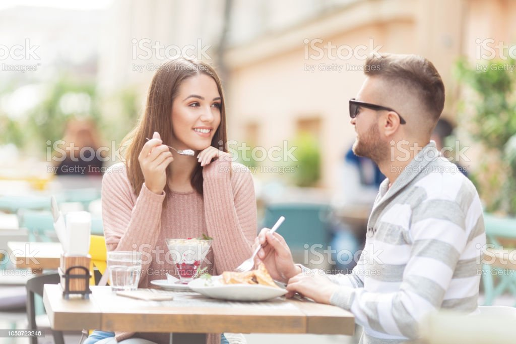 Young couple with sitting outdoors in a cafe and eaeting salad stock photo