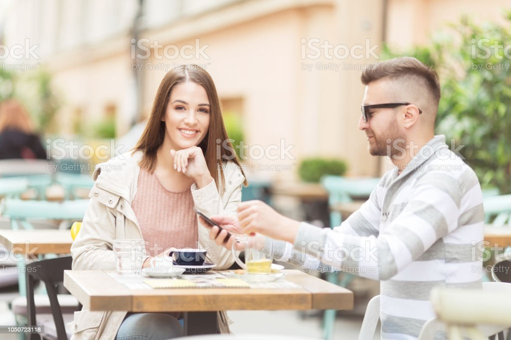 Young couple with sitting outdoors in a cafe stock photo