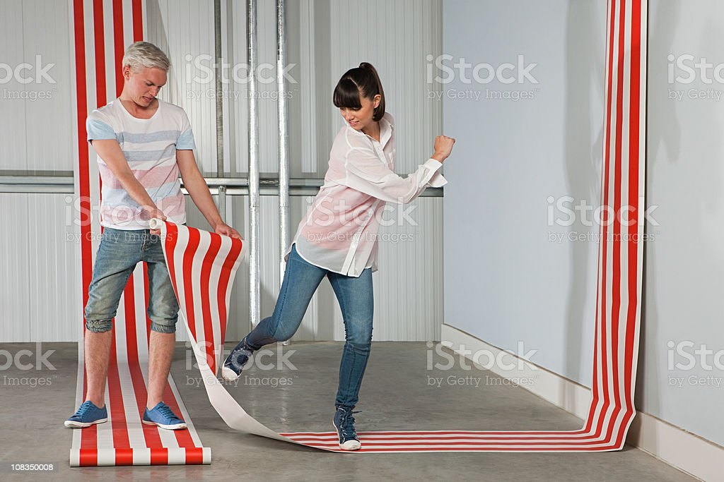 Young couple with striped wallpaper stock photo