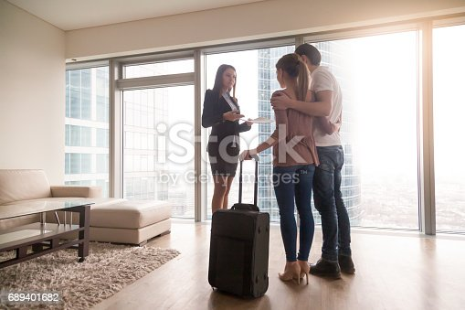 istock Young couple with suitcase meeting with female realtor, renting apartment 689401682