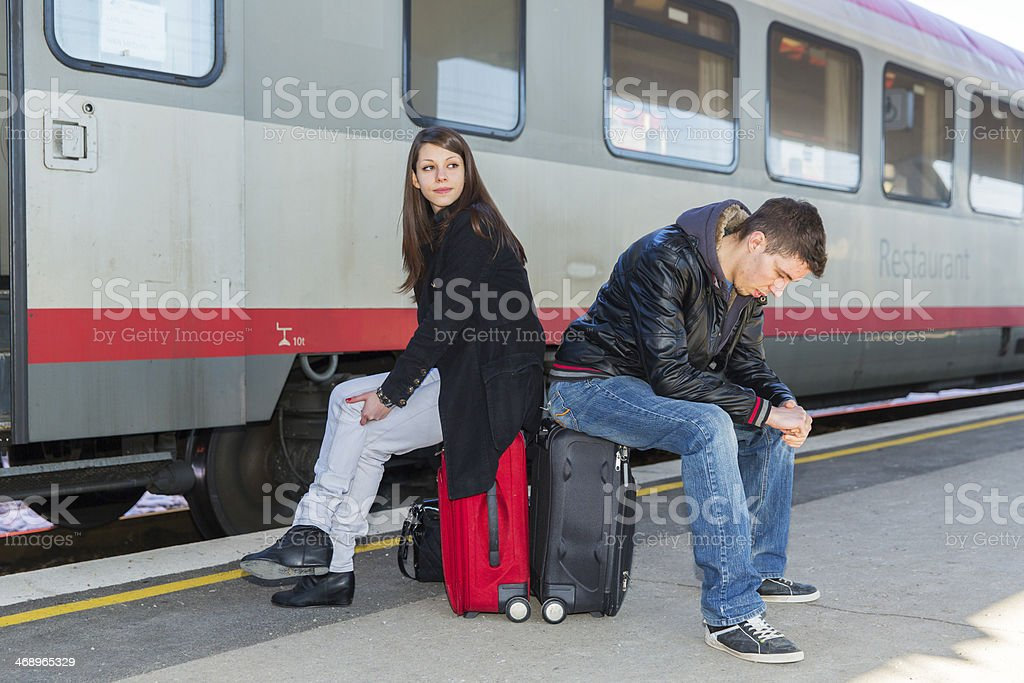 Young couple with suitcases waiting for a train...railway station royalty-free stock photo