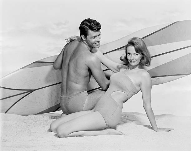 young couple with surfboard on beach, smiling - archival stock photos and pictures