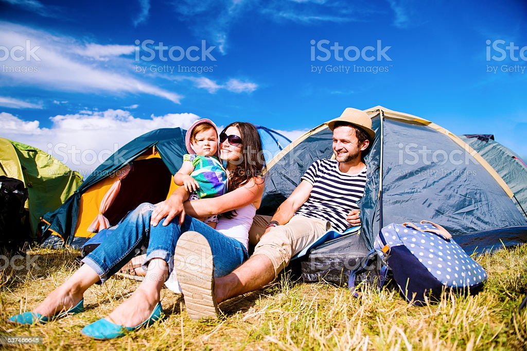 Young couple with their baby daughter in tent, summer Young couple with their baby daughter in a tent at summer music festival Adult Stock Photo
