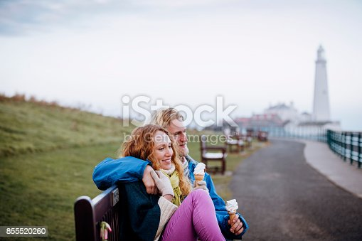 Young redheaded family enjoying eating ice-cream on the coast. Its cold outside so they are wrapped up warm. They kneel down with the children in front of  railings and smile at the camera
