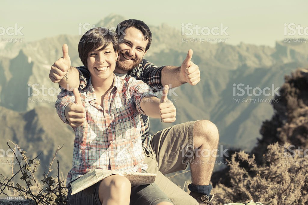 Young Couple with Thumbs Up at Top of Mountain royalty-free stock photo