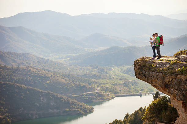 Young couple with toddler boy in sling standing on cliff stock photo