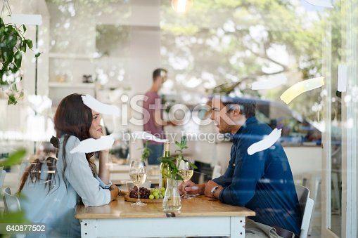 Side view of young man and woman looking at each other. Couple are sitting in coffee shop seen through glass window. Wine and grapes are served on table in cafe.