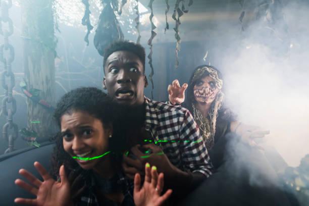junges paar mit zombie in halloween geisterhaus - freund kostüme stock-fotos und bilder