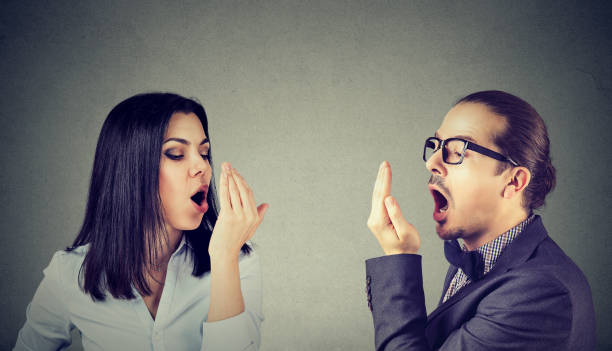 Young couple woman and man checking their breath stock photo