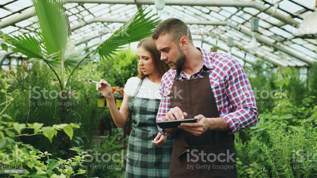 Young couple work in garden center. Attractive man cheking flowers and woman using tablet computer during working in greenhouse stock photo
