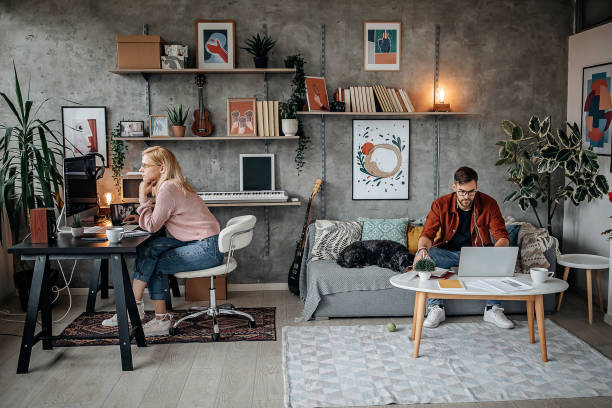 Young couple working from their home office during pandemic stock photo
