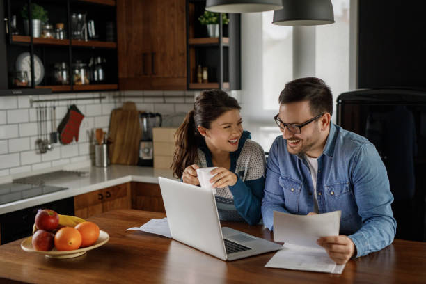 Young couple working on their finances together at home stock photo