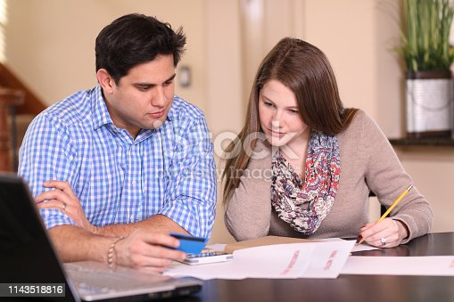 istock Young couple working out family finances together at home. 1143518816