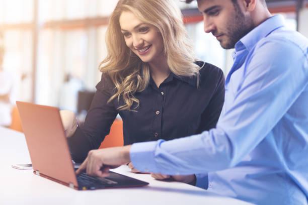 若いカップルがオフィスでラップトップに一緒に取り組んで.チームワークの概念。 ストックフォト