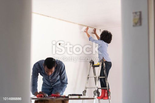 Young couple working together renovating their living room
