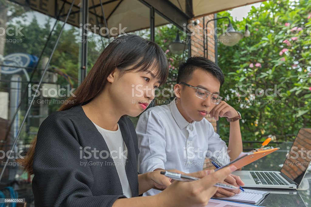 Young couple working with laptop at outdoor space of office stock photo