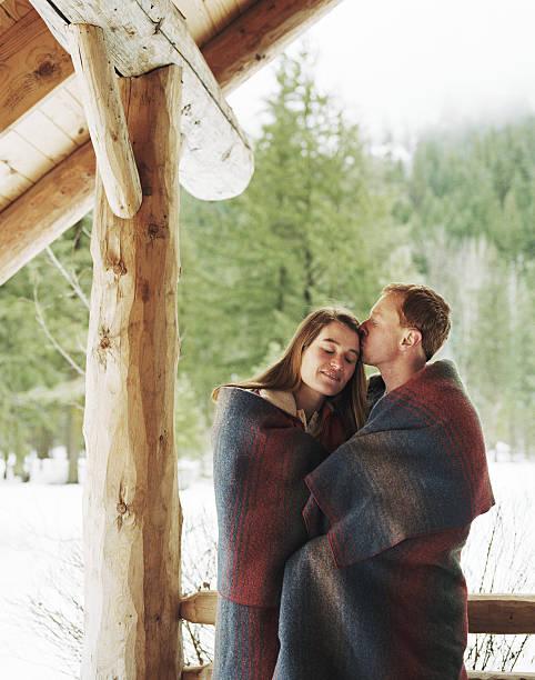 junges paar mit decke auf veranda, mann küssen - veranda decke stock-fotos und bilder