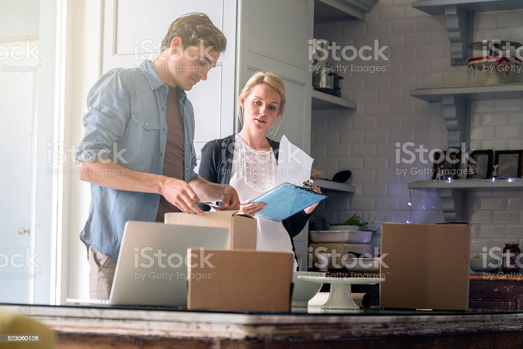 Young couple wrapping Christmas presents at home stock photo