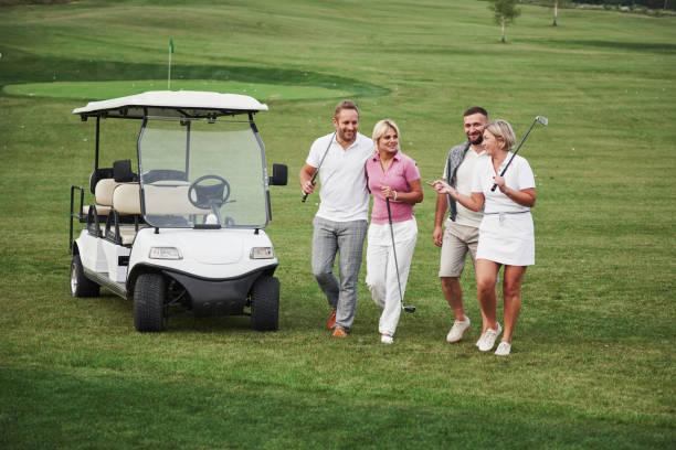 Junge Paare, die sich auf das Spiel vorbereiten. Eine Gruppe lächelnder Freunde kam auf einem Golfwagen ins Loch – Foto