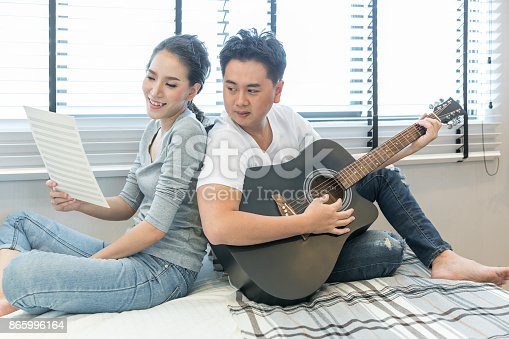 849355030 istock photo Young Couples playing guitar 865996164