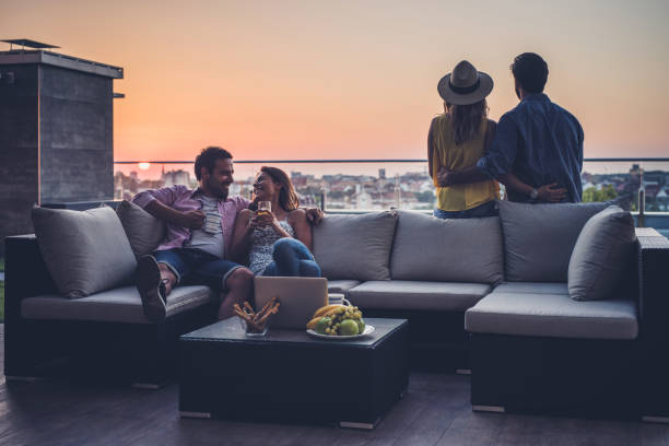 Young couples relaxing on a penthouse patio at sunrise. stock photo