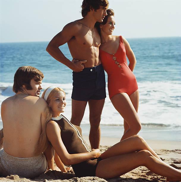 jovens casais na praia, sorridente em repouso - viagens anos 70 imagens e fotografias de stock