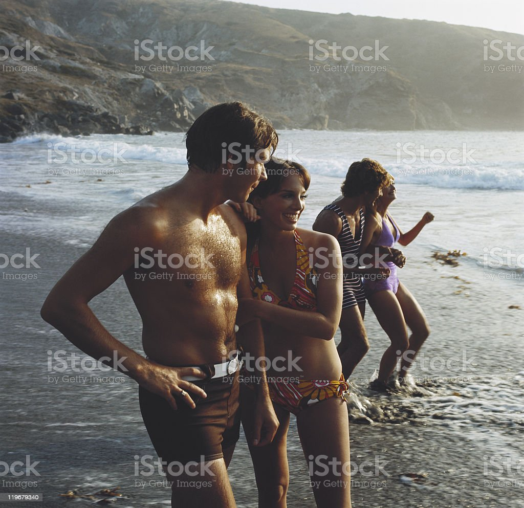 Young couples standing on beach, smiling stock photo