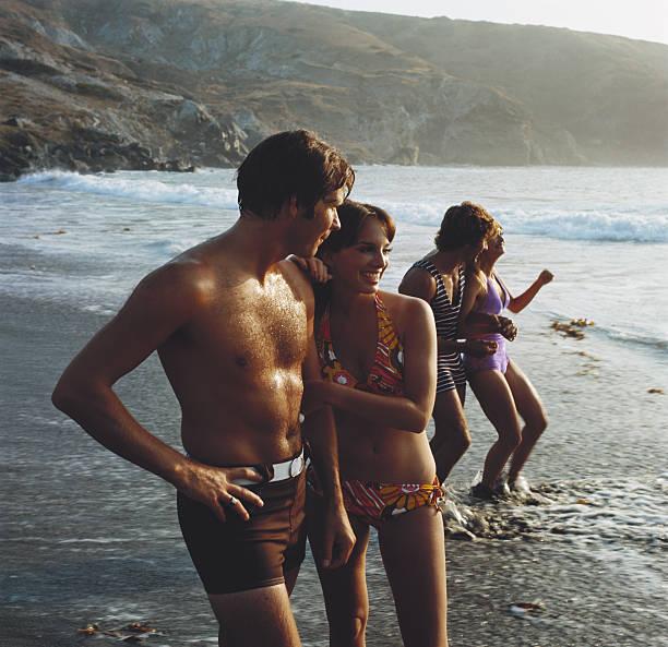 Jovem casal sorridente em pé na praia, - foto de acervo