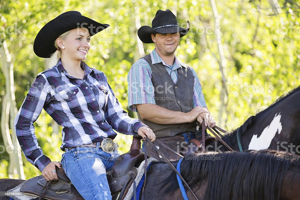 Young cowboy and cowgirl couple riding horses together royalty-free stock photo