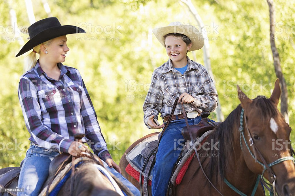 Young cowboy and cowgirl riding horses during trail ride stock photo
