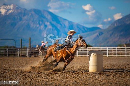 Young cowboy barrel racing at a local rodeo arena