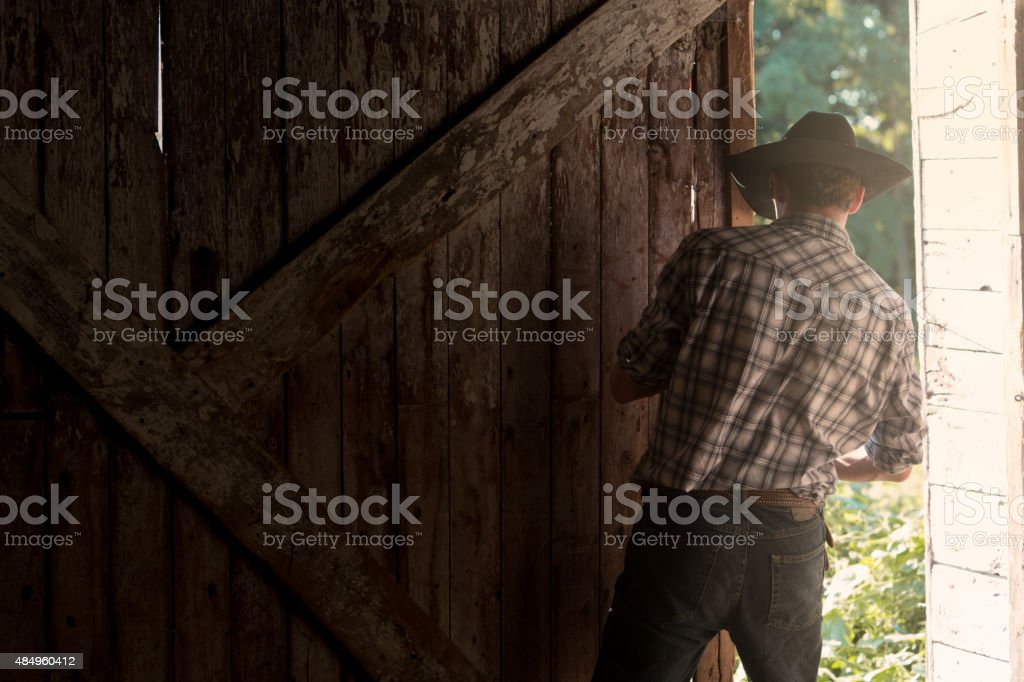 Young Cowboy Closing or Opening Barn Door stock photo