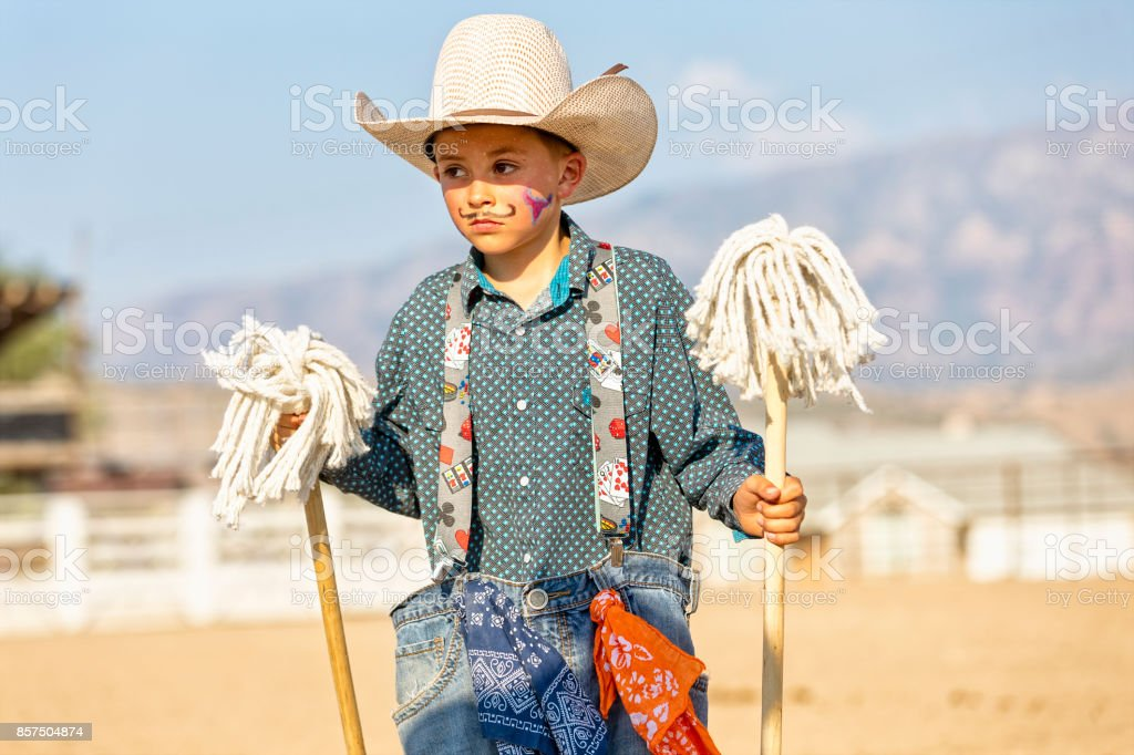 A young cowboy clown holding props used at intermission during a rodeo stock photo