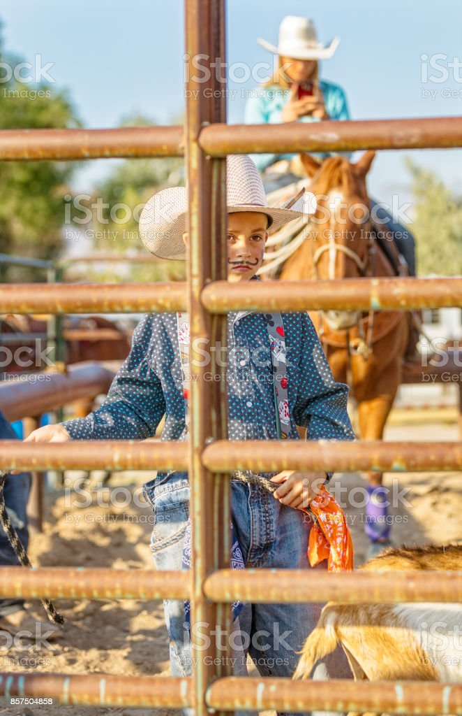 A young cowboy clown stands behind a gate with a goat during a rodeo stock photo