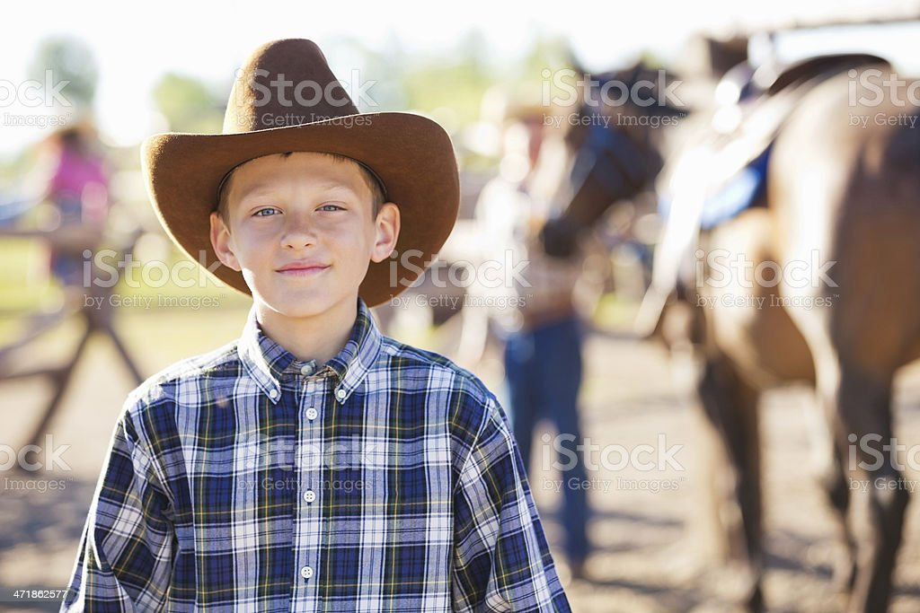 Young cowboy getting ready for trail ride at ranch royalty-free stock photo