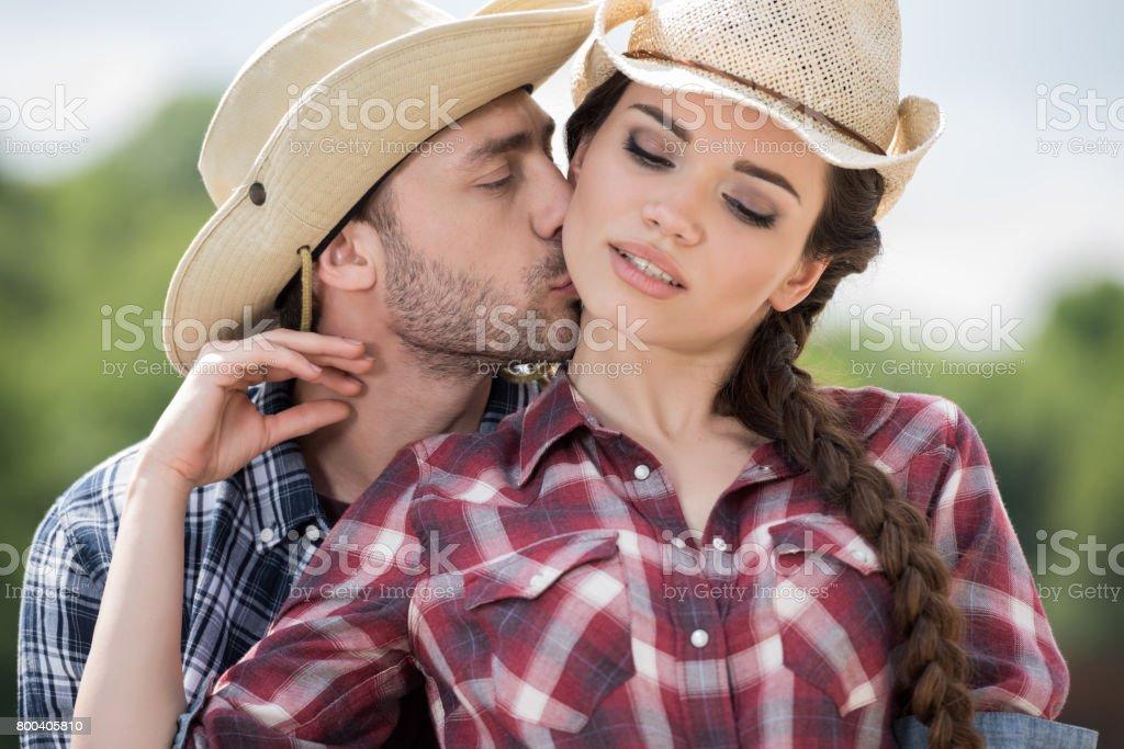 young cowboy kissing his sensual girlfriend outdoors at daytime stock photo