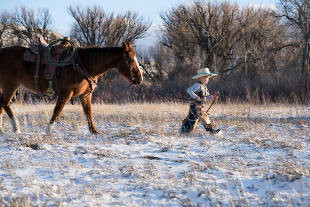 young cowboy leads a quarter horse - montana western usa stock pictures, royalty-free photos & images