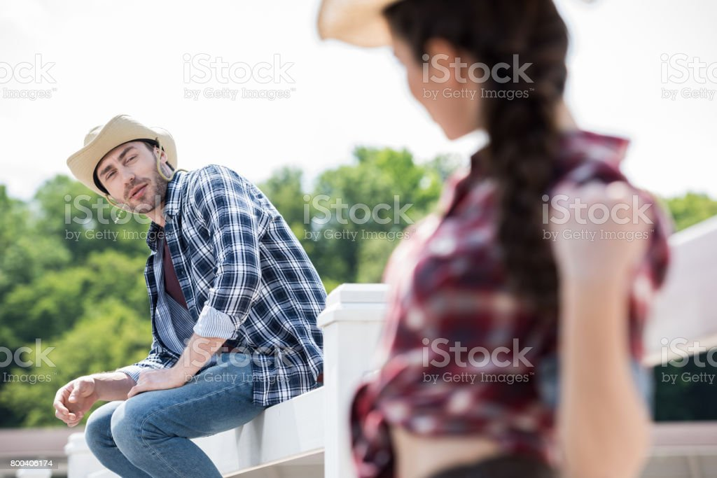 young cowboy looking at girl while sitting on fence at daytime stock photo