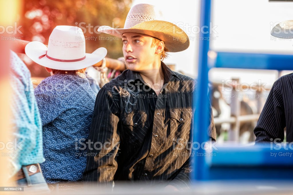 Young cowboy looks back behind the scenes of a rodeo stock photo