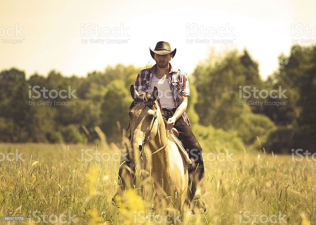 young cowboy man riding with horse stock photo