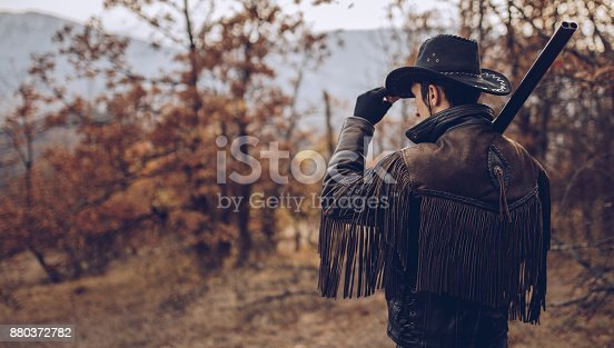 Young cowboy standing in woods and carrying shotgun